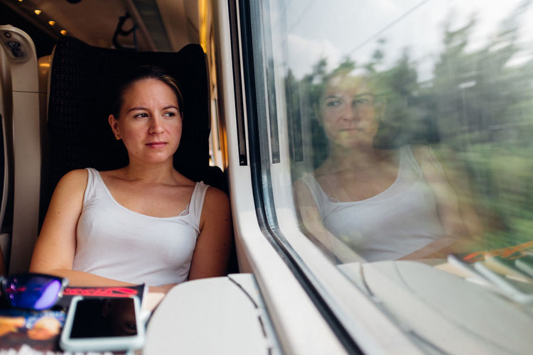 Backpacking Casual Clothing Day Europe Female Girl Headshot Journey Leisure Activity Lifestyles Mode Of Transport Portrait Public Transportation Sitting Train Transportation Travel Vehicle Interior Vehicle Seat Young Woman