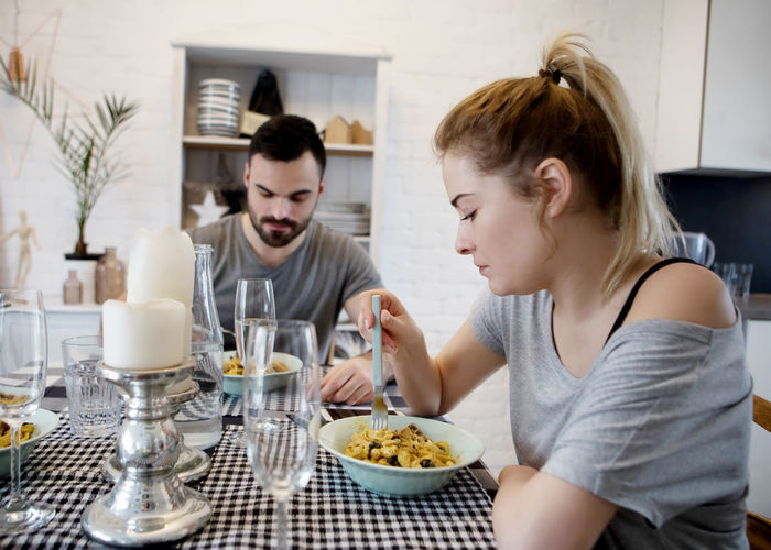 Close-up of young woman eating with man at home