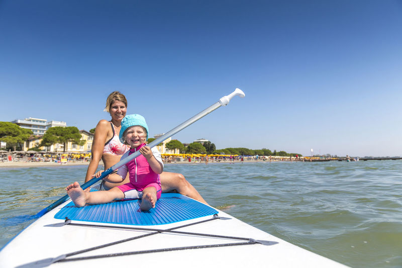 View  Of Happy Woman And Girl On Paddleboard