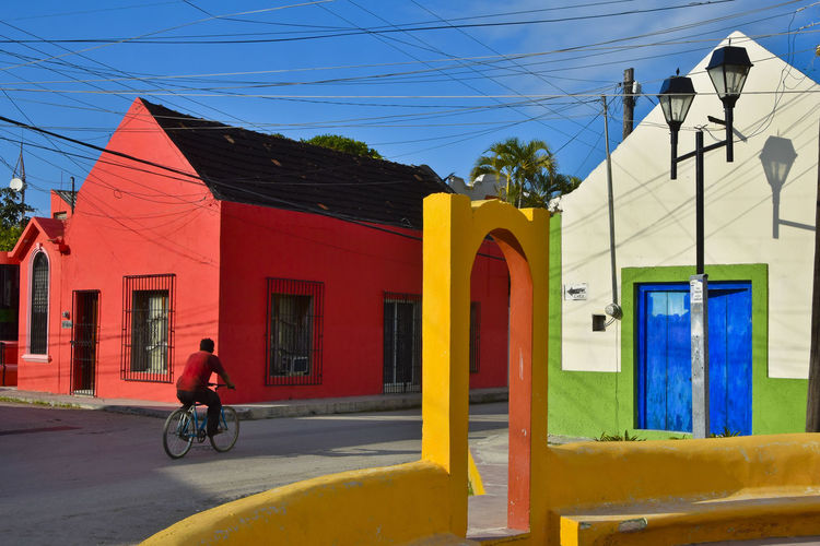 Person riding bicycle in small rural town of Yucatan, Mexico Architecture Daytime Green Red Street Light TOWNSCAPE Vivid Yellow Flower Arch Bicycle Bike Bird Colorful Day Riding Sky Small Town Stories Streetphotography Sunny Day Town Village Village Life Yucatan Mexico