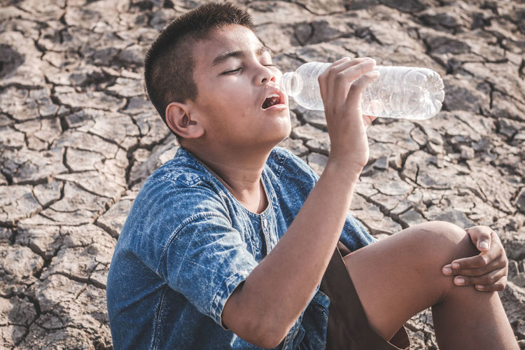 High Angle View Of Boy Drinking Water While Sitting On Barren Field