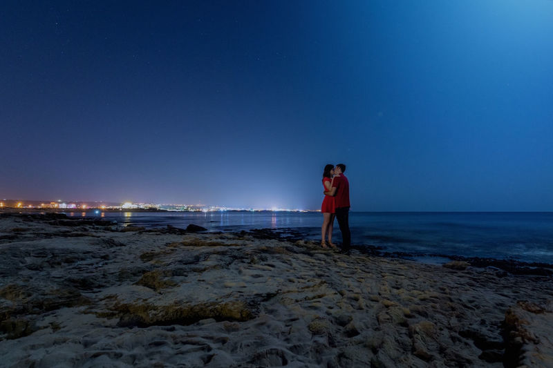 Couple kissing while standing at beach against clear blue sky