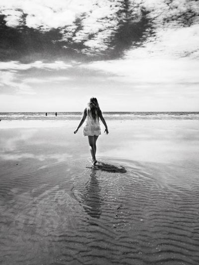 Rear view of woman walking on sea shore at beach against cloudy sky