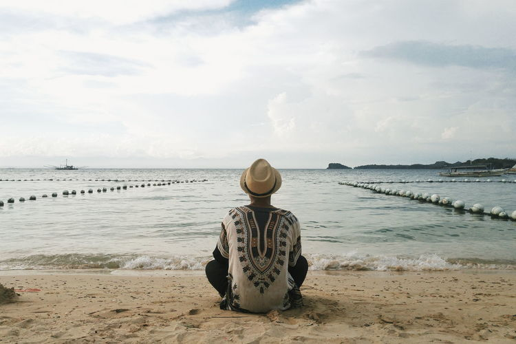 Rear View Of Man Sitting At Beach Against Cloudy Sky