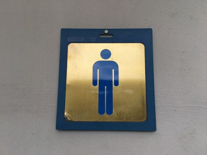 Close-up of male restroom symbol on wall