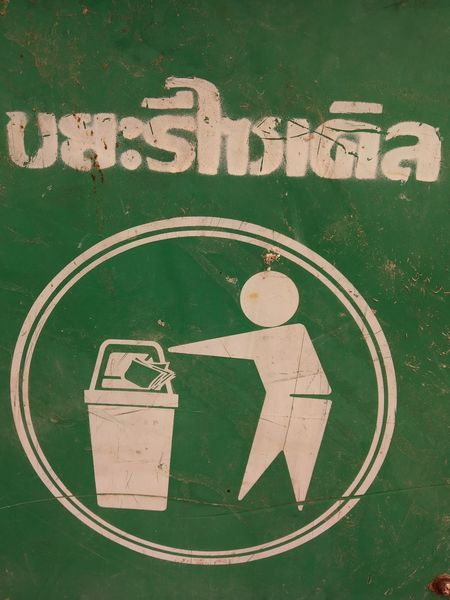 Thai label says recycle bin Information Medium Communication Text Close-up Green Color Logo Insignia Information Sign Badge Pedestrian Crossing Sign Information Symbol Directional Sign Sign Traffic Arrow Sign Non-western Script No Parking Sign Arrow Symbol Information Rusty Arrow Sign Signboard
