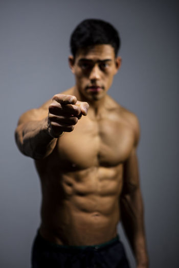 The muscular physique of a male fitness model put on display. The model points at the camera. Adult Asian  Athletic Body & Fitness Front Facing Human Body Looking At Camera Man Nam Vo Vietnamese Biceps Fit Fitness Model Front Facing Camera Grey Background Handsome Hunk Medium Shot Model Muscles Pointing Finger Serious Strong Toned Torso