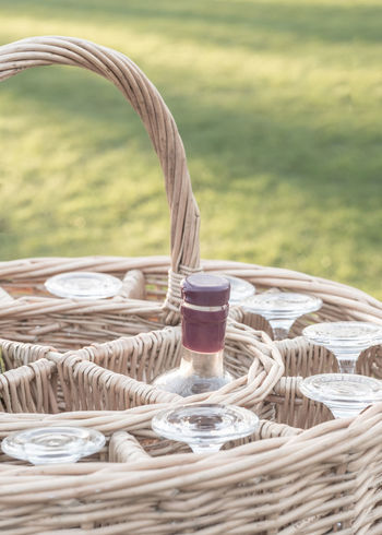 Wicker basket containing a wine bottle and some glasses Champagne Glasses Picnic Wine Bottle Wine Glass Wine Glasses Basket Close-up Day Hamper Macro No People Outdoors Picnic Picnic Basket Summer Wicker Basket Wineglass