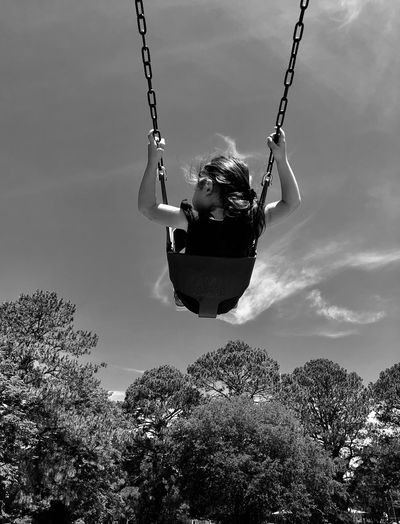 Low angle view of girl swinging against sky
