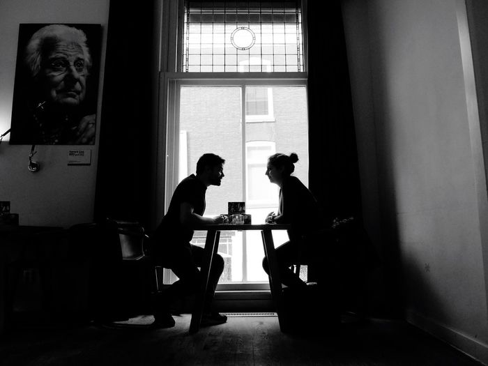 Side view of couple sitting on chairs by table against window at home