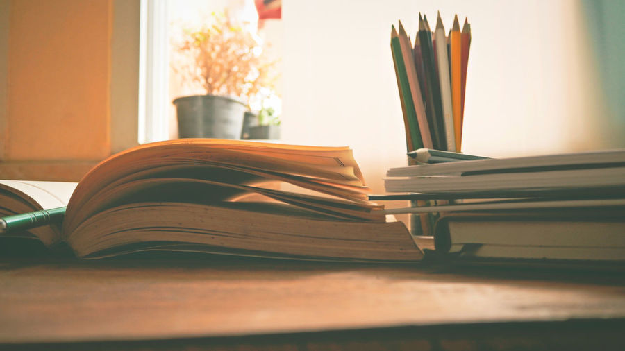 A book is opening on desk in a summer Book Book Cover Close-up Day Desk Desk Organizer Education Indoors  Knowledge Learning Literature No People Page Research Stack Studying Table