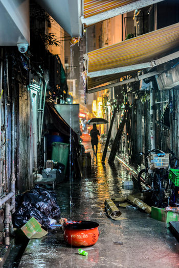 Woman with umbrella on alley amidst buildings in city at night during rainy season
