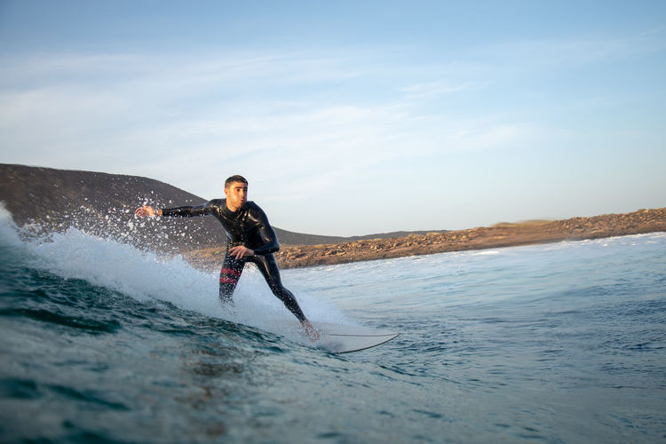 Real People One Person Sea Sport Water Leisure Activity Lifestyles Sky Waterfront Motion Surfing Beauty In Nature Full Length Aquatic Sport Nature Young Adult Day Men Skill  Outdoors