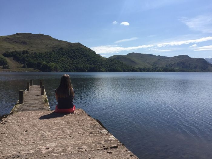 Rear view of woman sitting on jetty at lake against blue sky during sunny day