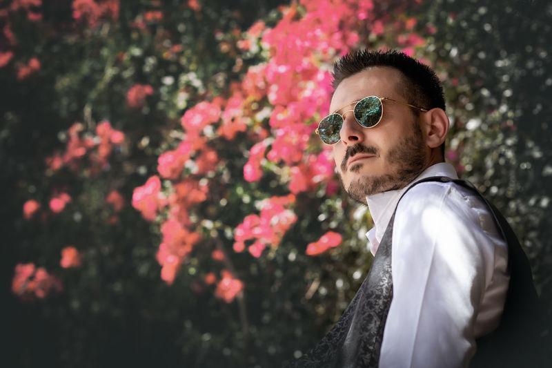 Side view of man wearing sunglasses by flowering tree