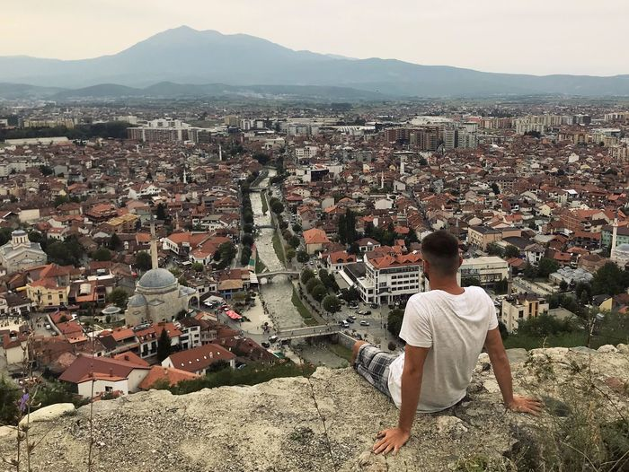 Read view of young man watching at panoramic view of town prizren in kosovo