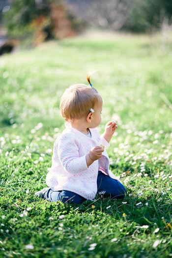 Boy sitting on grass in field