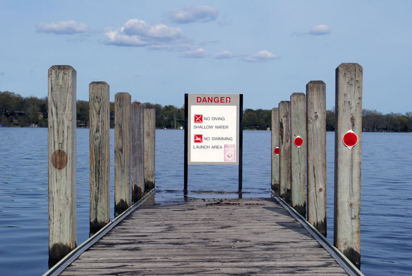 Communication Day Dock Lake Nature No People No Swimming Outdoors Pier Safety Sky Text Warning Water Waterfront Wood - Material Wooden Post