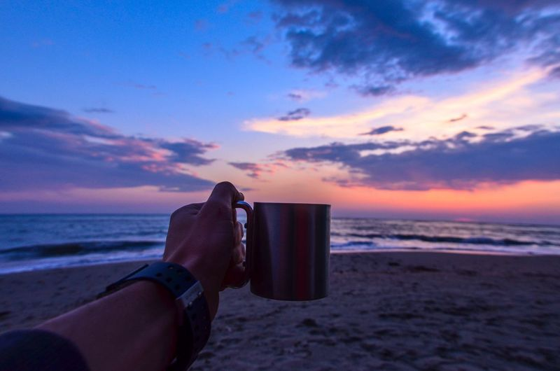 Cropped Image Of Hand Holding Cup At Beach