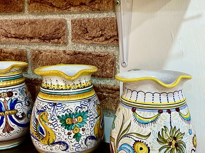 Close-up of multi colored jars on wall
