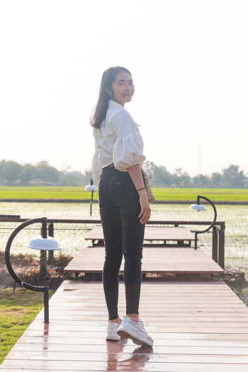 Full length of woman standing on bench against sky