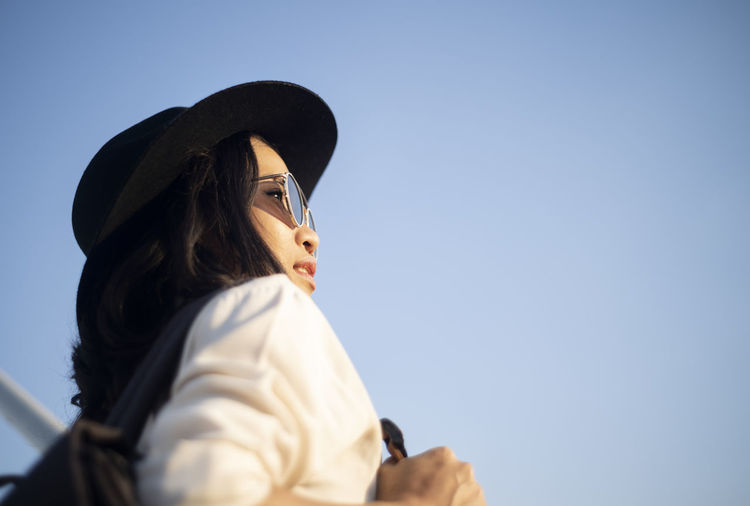 Portrait of woman wearing hat against sky