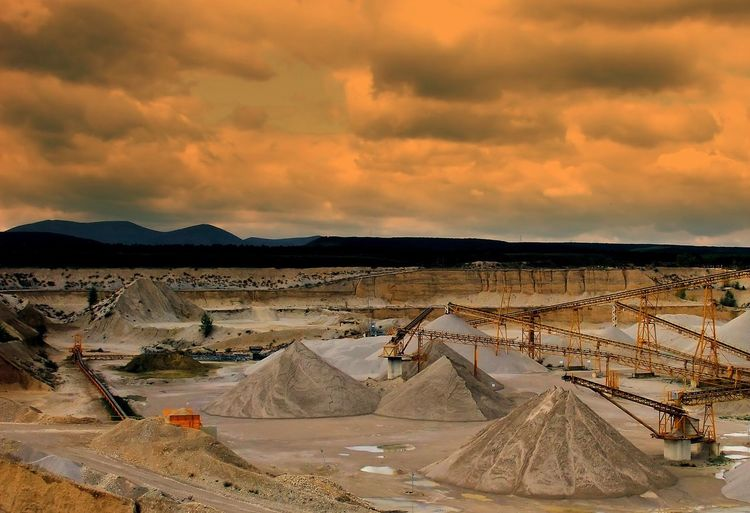 Cranes In Coal Mine Against Cloudy Sky During Sunset