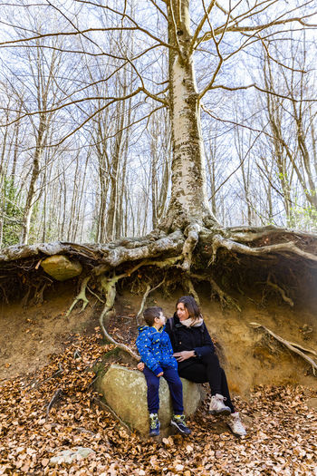 Mom and son under a big tree Montseny Autumn Two People Tree Togetherness Full Length Men Adult Plant Leisure Activity Young Adult Casual Clothing Nature Land Forest Young Men Males  People Sitting Real People Women Couple - Relationship Outdoors Positive Emotion Roots