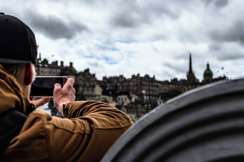 Cropped Image Of Man Photographing City Through Mobile Phone