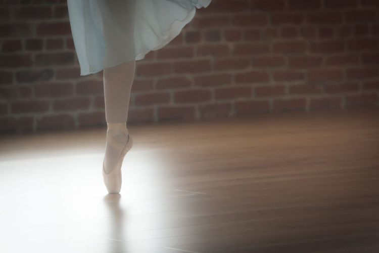 Low section of woman practicing tiptoeing in dance studio
