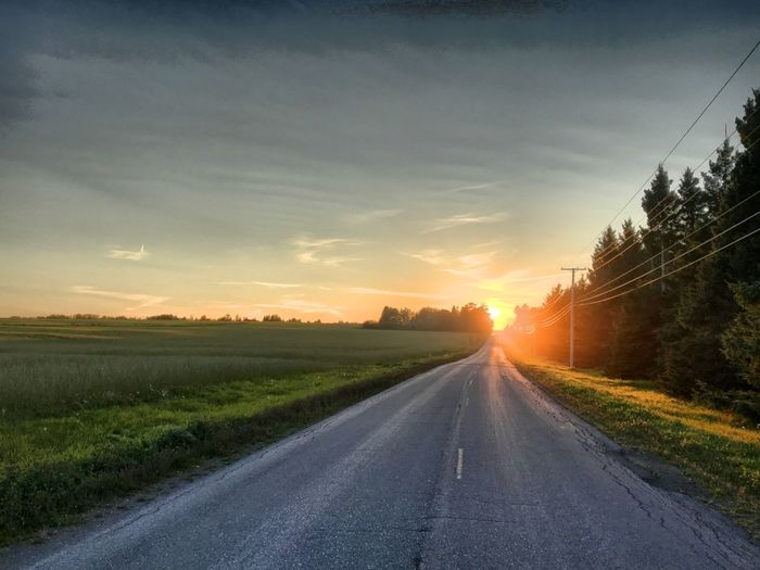Country road amidst field against sky during sunset