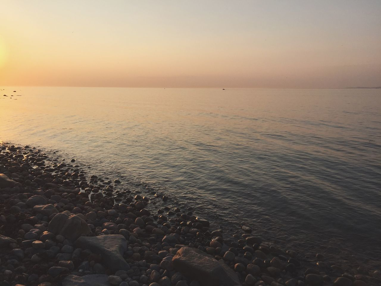 sea, beach, water, nature, tranquil scene, beauty in nature, tranquility, scenics, sunset, shore, horizon over water, pebble, outdoors, idyllic, pebble beach, sand, no people, sky, day, clear sky