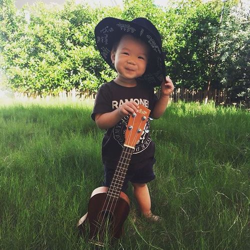 Boys Childhood Day Front View Full Length Grass Guitar Happiness Music Musical Instrument Musician Nature One Person Outdoors People Playing Plucking An Instrument Portrait Real People Smiling Standing Tree