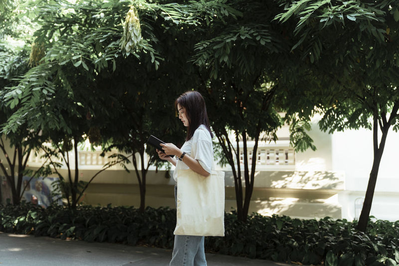 Side view of woman reading book while walking outdoors