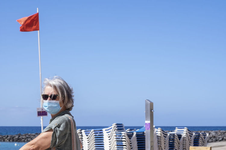 Woman standing at beach against clear blue sky