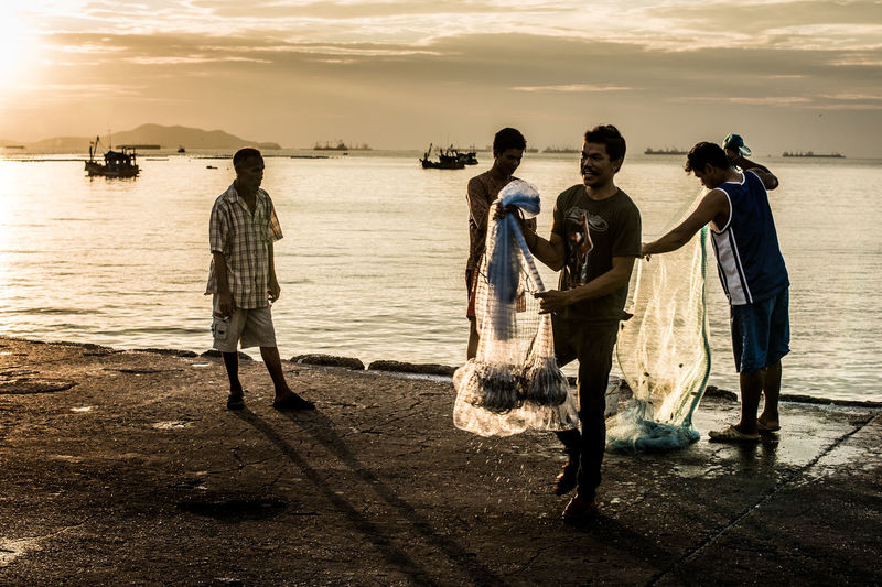 Group of Fisherman with net at sea Fisherman Fishing Nets Fishing Time Folkwang Hobby Jetty Job Leisure Activity Man Net Ocean Outdoors Port Sea Sky Sky And Clouds Sun Sunset Sunset Silhouettes Sunset Tine Time Water Wave Learn & Shoot: Working To A Brief