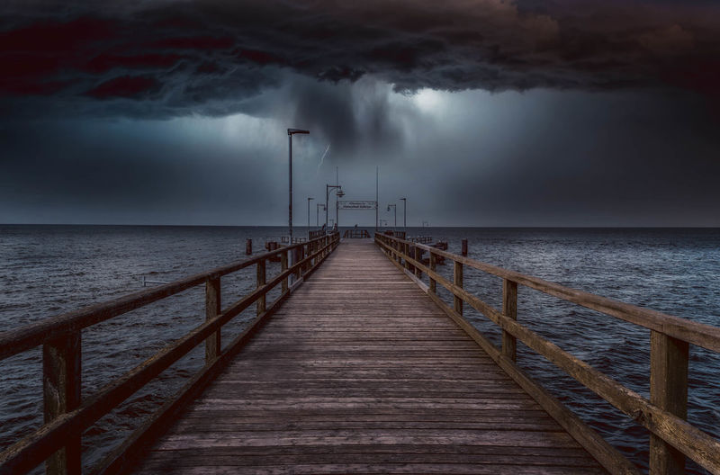 Pier over sea against storm clouds