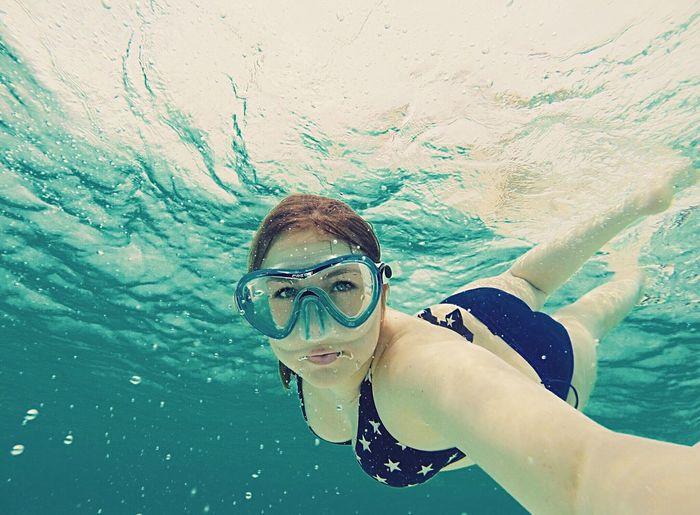 Portrait of woman wearing bikini swimming in sea