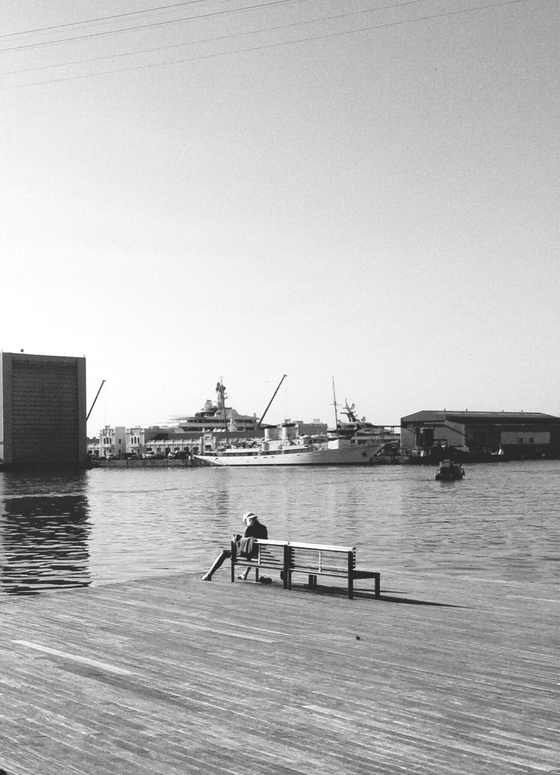 water, built structure, architecture, copy space, clear sky, men, building exterior, lifestyles, pier, leisure activity, nautical vessel, river, sitting, person, rear view, bench, lake