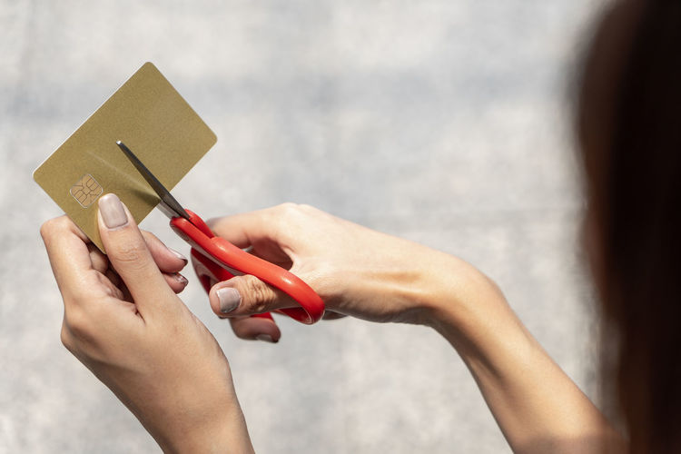 Close-up of woman cutting credit card