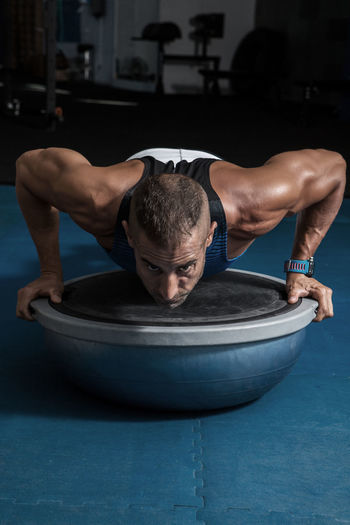 Determined Man Doing Push-Ups On Bosu Ball At Gym