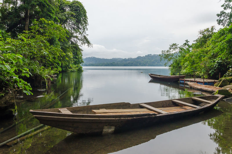 Simple Wooden Boats Moored In Barombi Mbo Crater Lake Against Cloudy Sky, Cameroon, Africa