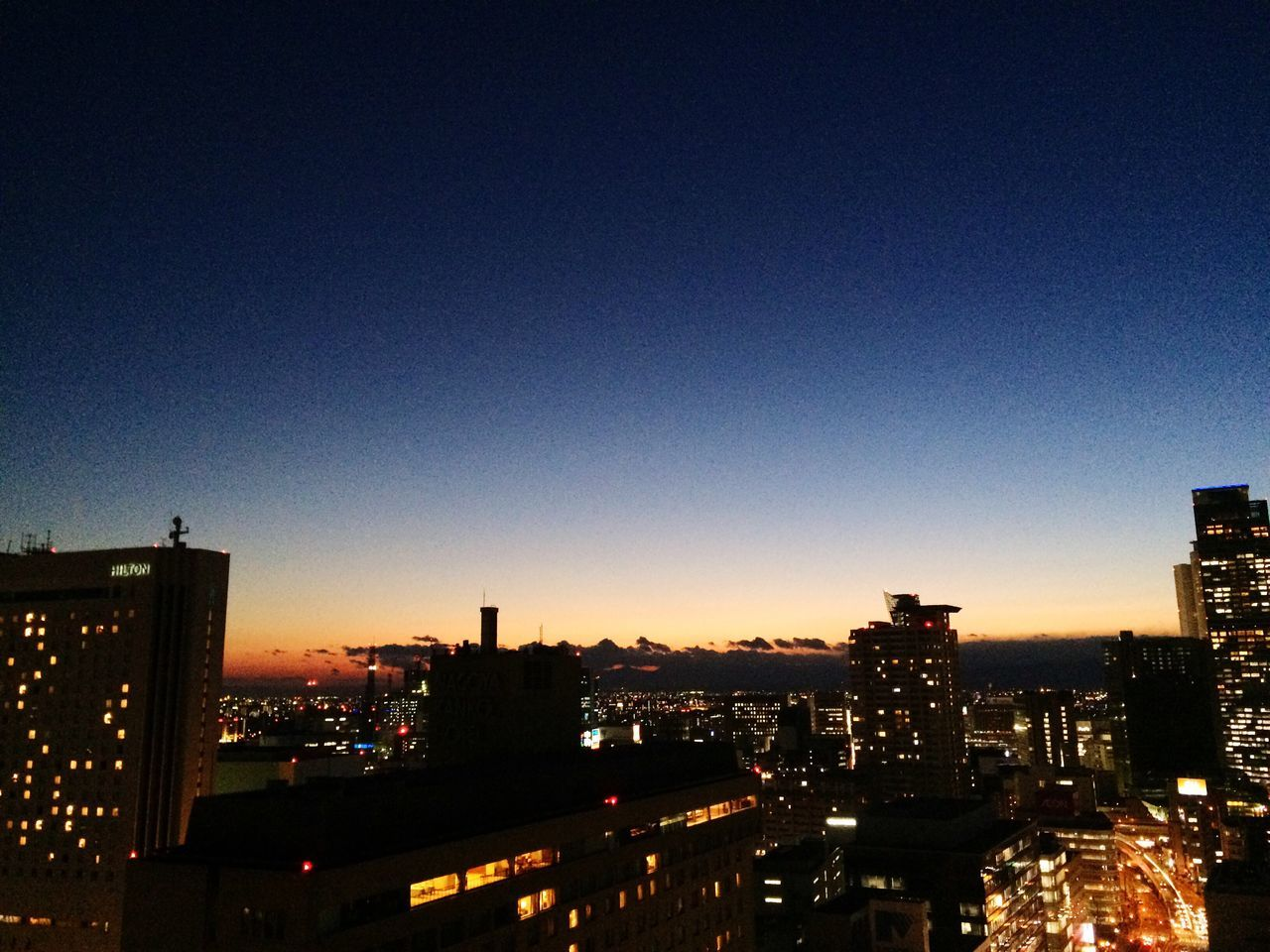 illuminated, architecture, building exterior, cityscape, city, built structure, night, skyscraper, no people, clear sky, outdoors, sunset, sky, blue, urban skyline