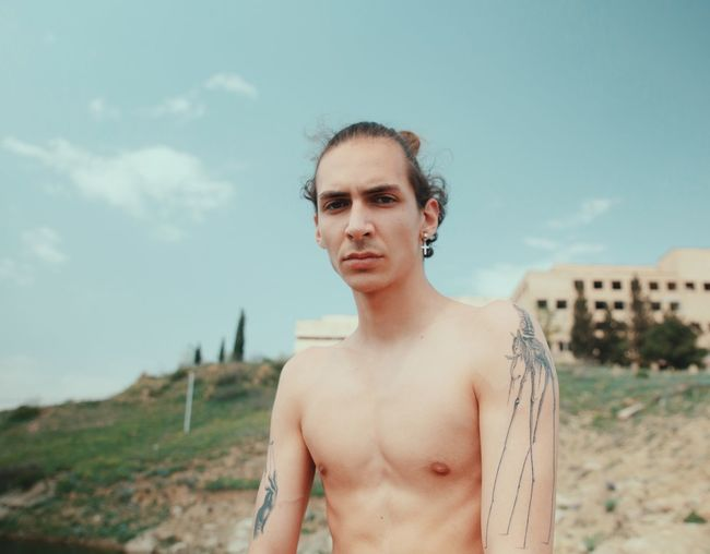 Portrait of shirtless man standing on land against sky