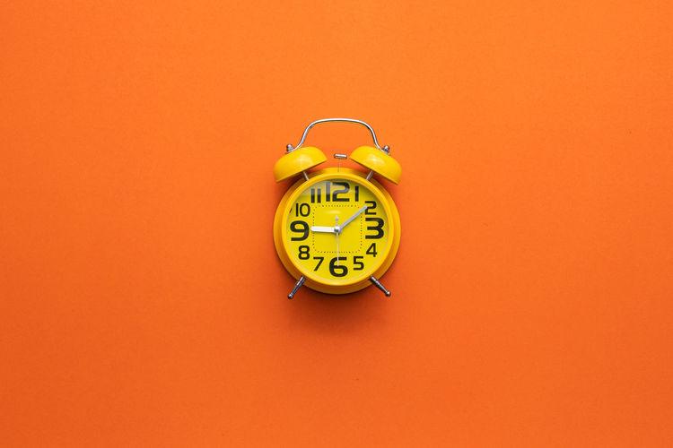 Close-up of clock on orange wall