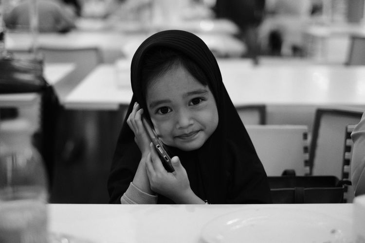 Portrait of smiling girl using phone sitting at restaurant