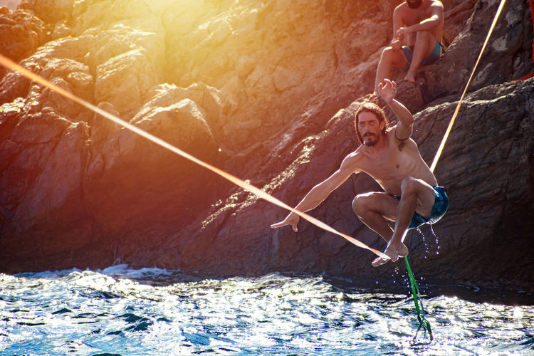 High angle view of shirtless man holding rope in water