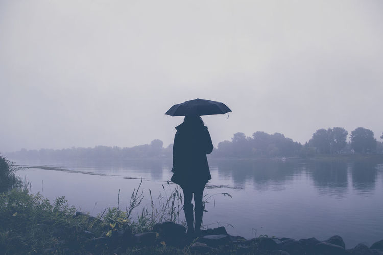 Silhouette Woman Standing By Lake Against Sky