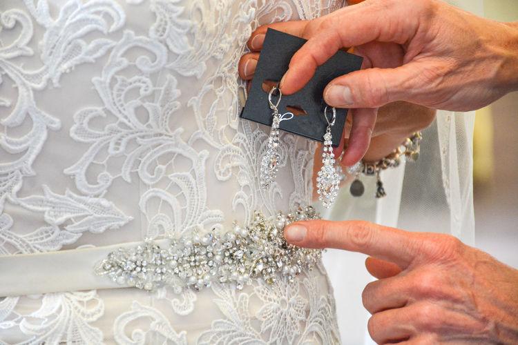 Cropped hands examining wedding dress