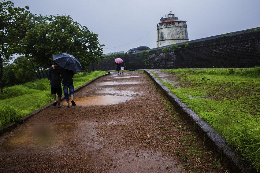 16th Century Goa Rain Aguada Fort Architecture Building Exterior Built Structure Grass Men Outdoors Sky The Way Forward Umbrella Walking Water
